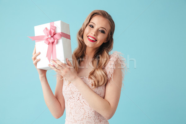 Smiling blonde woman in dress holding gift box Stock photo © deandrobot