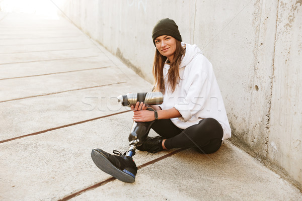 Photo of smiling young handicapped woman having bionic leg in st Stock photo © deandrobot