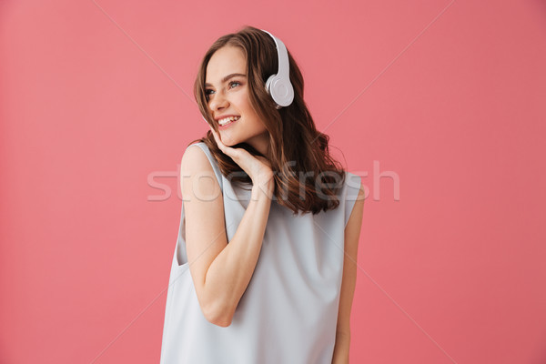 Beautiful positive young woman listening music. Looking aside. Stock photo © deandrobot