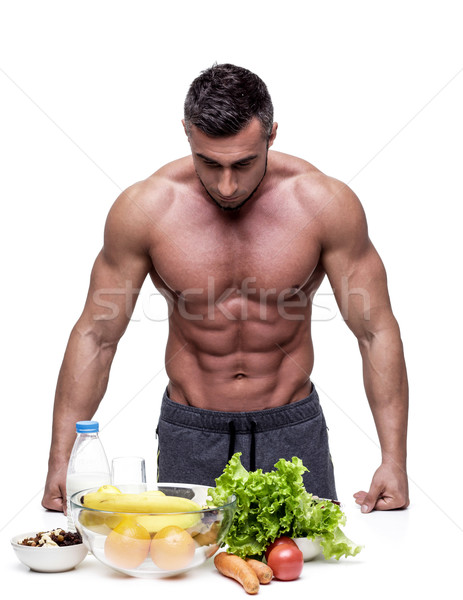 Pensive muscular man leaning on the table with healthy food Stock photo © deandrobot