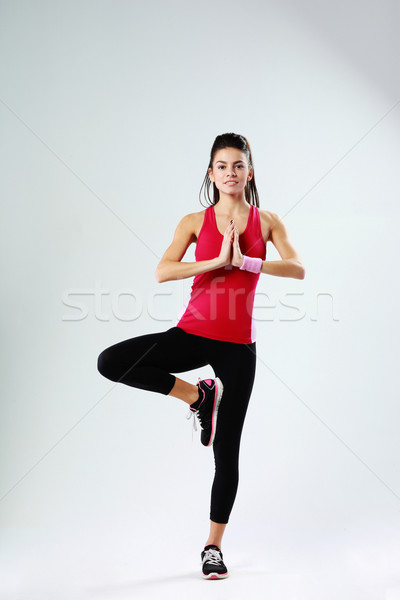 Young sport woman meditating while standing on one leg on gray background Stock photo © deandrobot