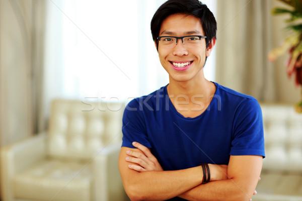 Heureux asian homme permanent bras pliées Photo stock © deandrobot
