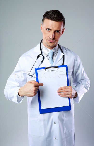 Dissatisfied male doctor showing on empty clipboard on gray background Stock photo © deandrobot