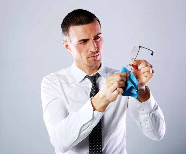 Handsome businessman wiping eyeglasses with rag on gray background Stock photo © deandrobot