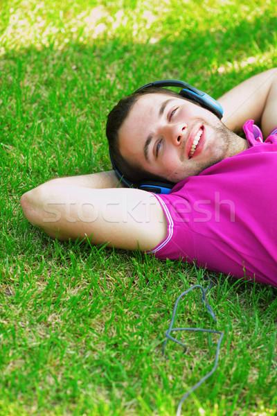 Portret młody człowiek słuchanie muzyki trawy uśmiech technologii Zdjęcia stock © deandrobot