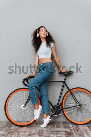 Happy woman stnading with bicycle  Stock photo © deandrobot