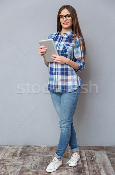 Full lenght portrait of beautiful smart girl holding tablet Stock photo © deandrobot
