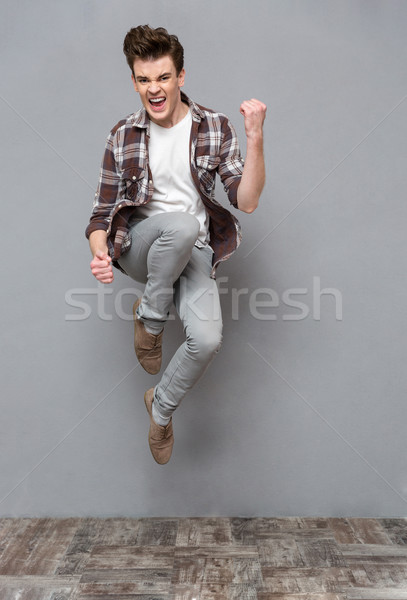 Positive casual young man jumping in the air and smiling Stock photo © deandrobot