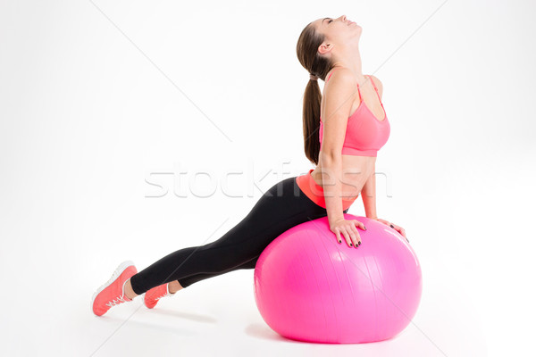 Focused attractive young fitness woman doing stretching on pink fitball  Stock photo © deandrobot