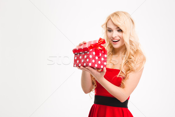Happy excited young blonde female in red dress opened present  Stock photo © deandrobot