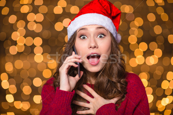 Surprised girl in santa claus hat talking on mobile phone  Stock photo © deandrobot