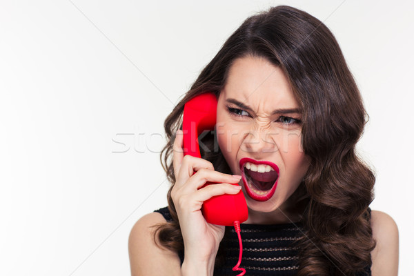 Angry woman in retro style screaming and talking on telephone Stock photo © deandrobot