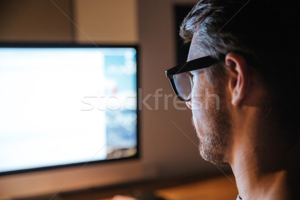 Concentrated man sitting and looking at screen of monitor Stock photo © deandrobot