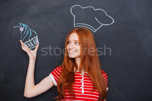 Woman in drawn chef hat holding drawing cupcake over blackboard  Stock photo © deandrobot