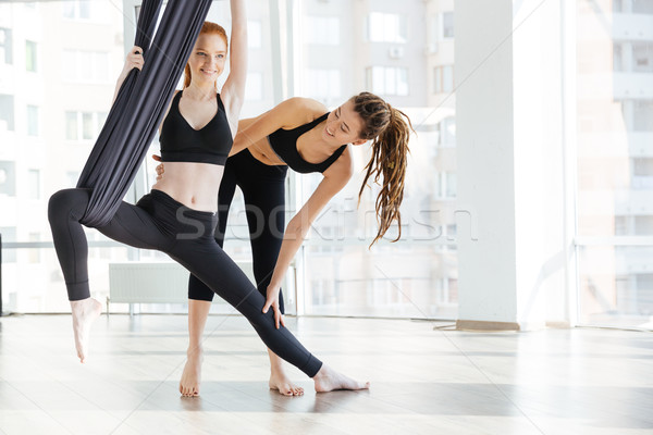 Happy woman doing aerial yoga with trainer in studio Stock photo © deandrobot