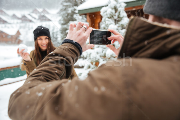 Man holding mobile phone and taking pictures of his girlfriend  Stock photo © deandrobot