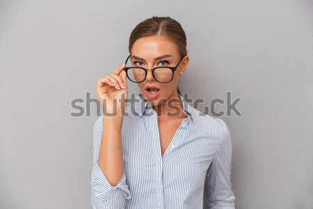 Funny teenage girl in glasses making moustache with her finger  Stock photo © deandrobot