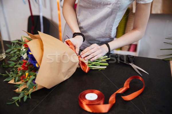 Woman florist making bouquet of flowers using red ribbon  Stock photo © deandrobot