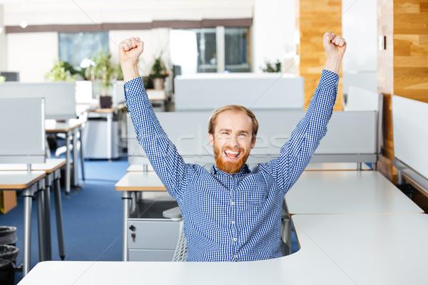 Empresário sessão as mãos levantadas sucesso escritório Foto stock © deandrobot