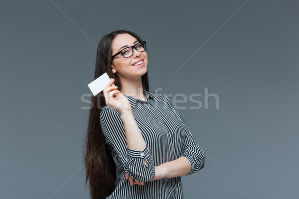 Gülümseyen kadın boş kart gri bakıyor kamera Stok fotoğraf © deandrobot
