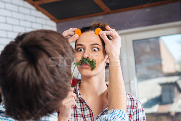 Playful couple having fun and making funny face on kitchen Stock photo © deandrobot