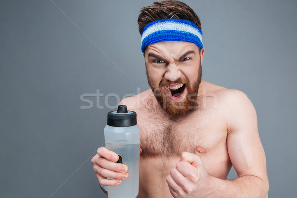 Angry shirtless young sportsman holding bottle of water and shouting Stock photo © deandrobot