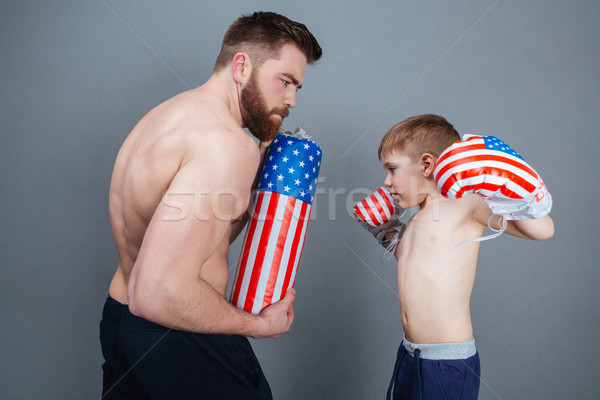 Father and son in boxing gloves training using punching bag Stock photo © deandrobot