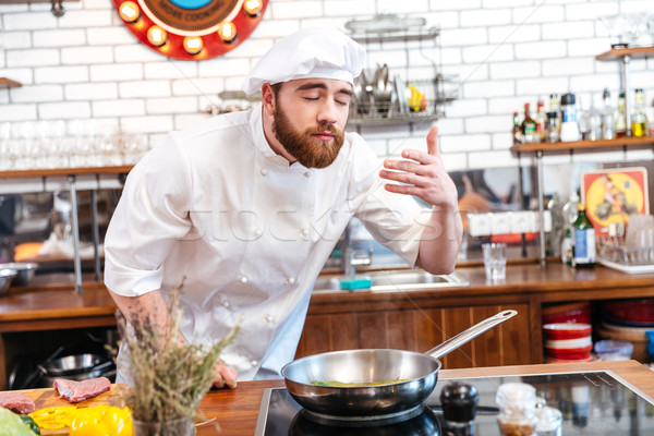 Happy inspired chef cook cooking and smelling aromas of food  Stock photo © deandrobot