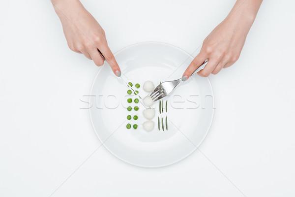 Mulher mãos alimentação verde ervilhas Foto stock © deandrobot