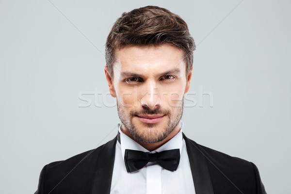 Closeup of attractive confident young man in tuxedo with bowtie Stock photo © deandrobot
