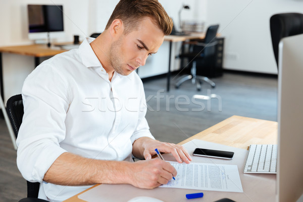 Businessman sitting and signing documents in office Stock photo © deandrobot