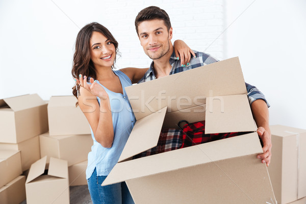 Couple showing keys to new home hugging looking at camera Stock photo © deandrobot