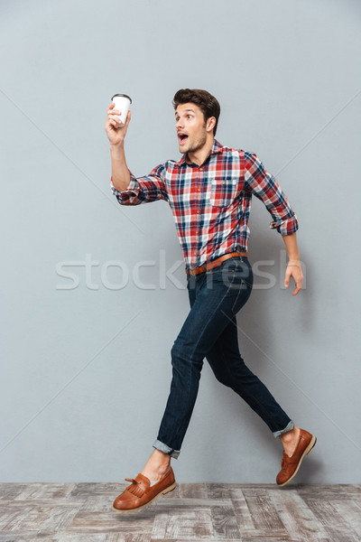 Attractive young man holding cup of takeaway coffee and running Stock photo © deandrobot
