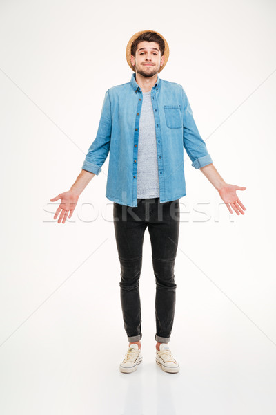 Confused cute young man in jeans shirt standing and shrugging Stock photo © deandrobot