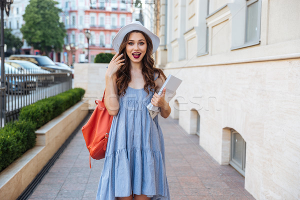 Happy surprized woman with backpack and magazines standing on street Stock photo © deandrobot