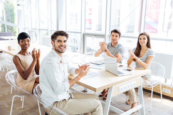 Happy young business people clapping hands on presentation in office Stock photo © deandrobot