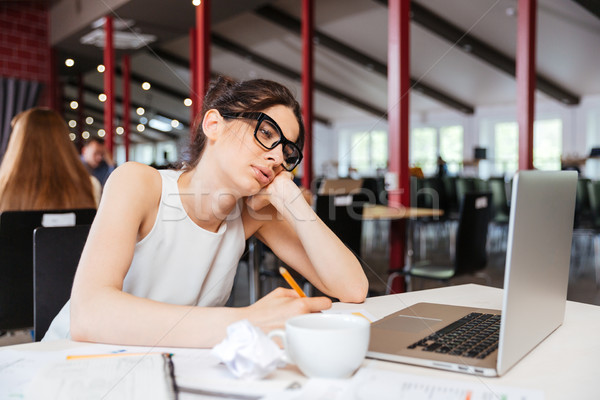 Bored businesswoman working using laptop in office Stock photo © deandrobot