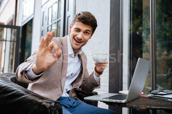 Man showing ok sign and using laptop in outdoor cafe Stock photo © deandrobot