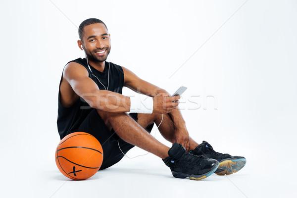 Férfi kosárlabdázó ül zenét hallgat okostelefon mosolyog Stock fotó © deandrobot