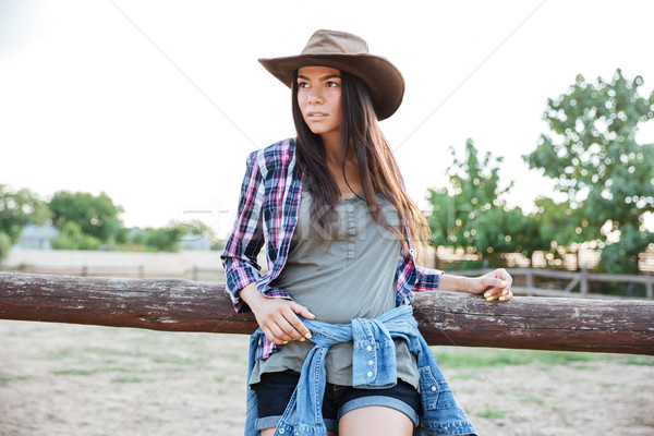 Beautiful young woman cowgirl in hat and checkered shirt Stock photo © deandrobot