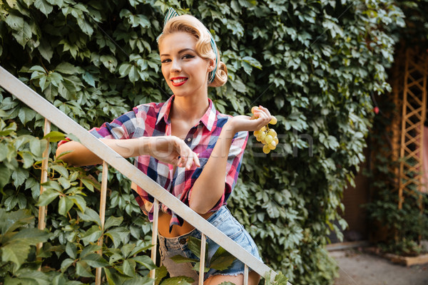 Pin up girl with bunch of grape in the garden Stock photo © deandrobot