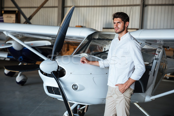 Serious man standing near small airplane Stock photo © deandrobot