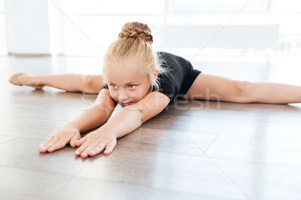 Little ballerina stretching and doing twine in dance studio Stock photo © deandrobot
