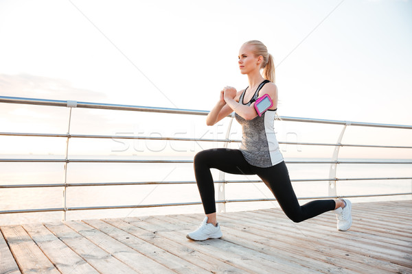 Attractive young sportswoman stretching legs on pier Stock photo © deandrobot