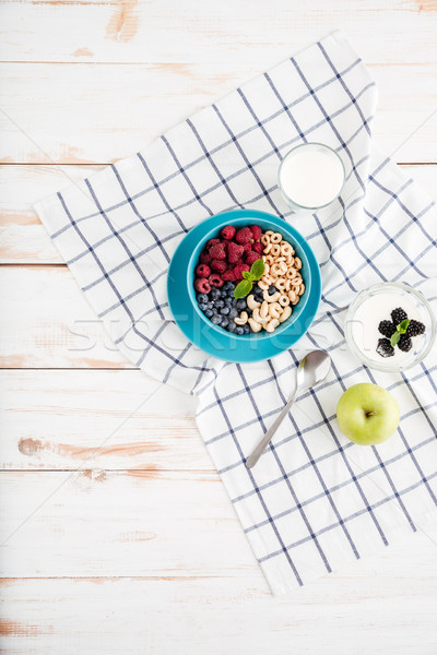 Top view of granola, berries, apple and milk Stock photo © deandrobot
