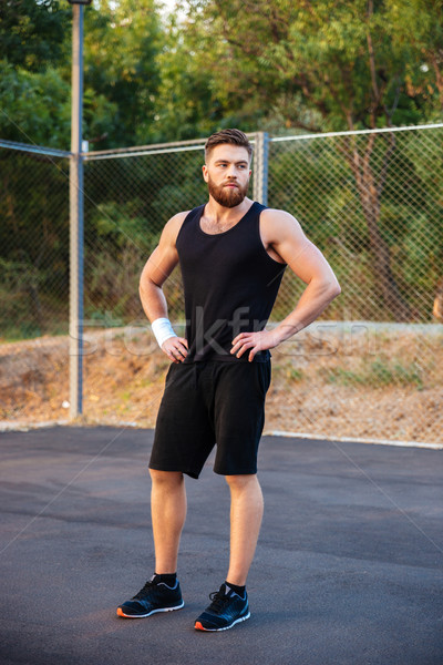 Concentrated bearded man in sportswear standing with hands on hips Stock photo © deandrobot