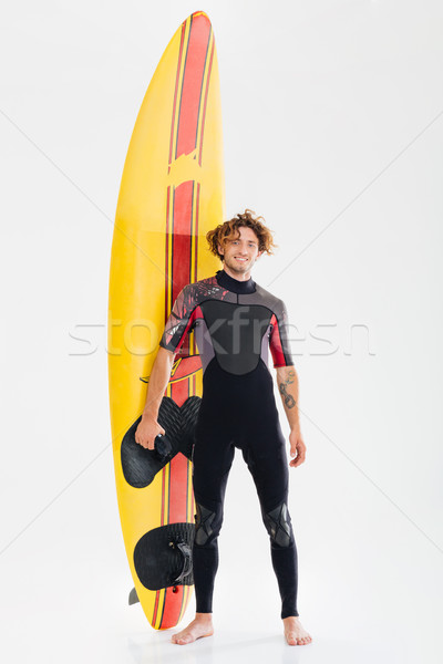 Full length portrait of a happy surfer holding surf board Stock photo © deandrobot
