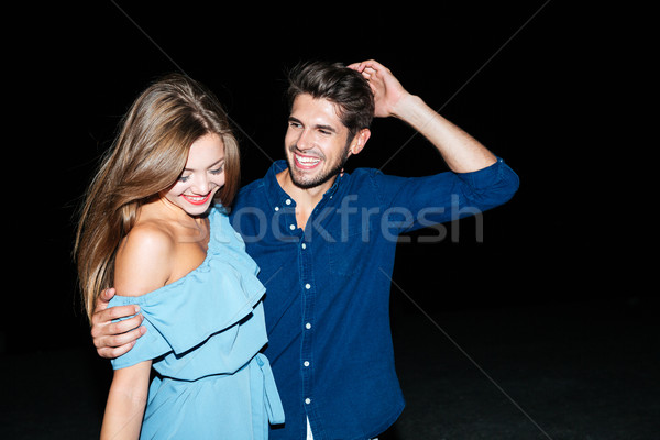 Happy couple standing and embracing at night on the beach Stock photo © deandrobot