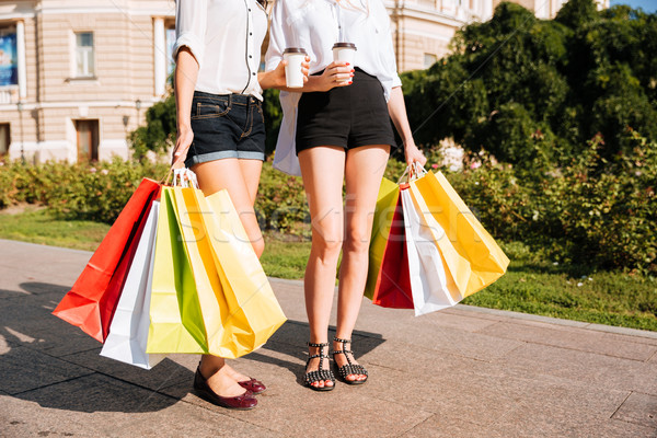 Two young female walking along street with shopping bags Stock photo © deandrobot
