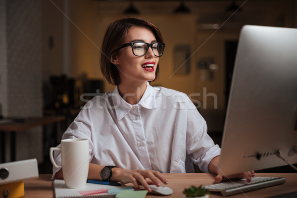 Cheerful young businesswoman using computer and smiling in office Stock photo © deandrobot